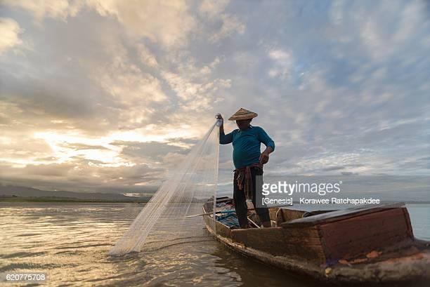 A fisherman preparing his net in the morning sunrise