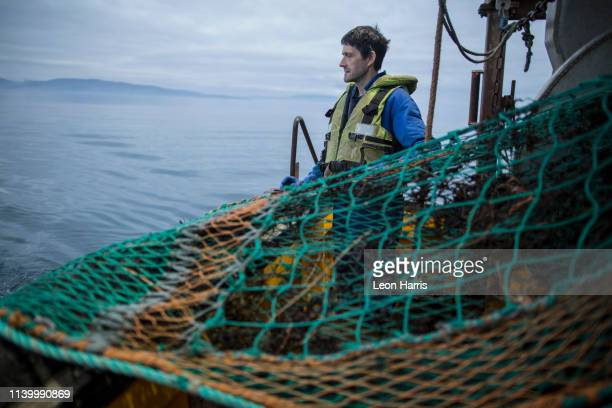 fisherman preparing net, isle of skye, scotland - fishing boat stock pictures, royalty-free photos & images