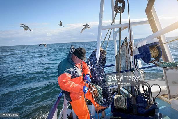 Fisherman preparing nets on trawler
