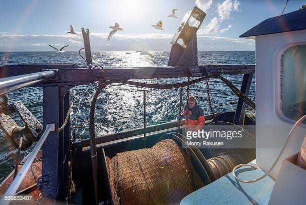 Fisherman preparing nets on trawler