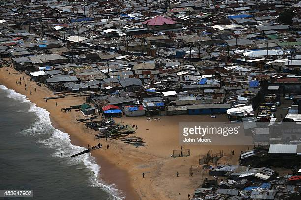 Fisherman pull a dugout from the water in the impoverished neighborhood of West Point on August 15 2014 in Monrovia Liberia People in the area...