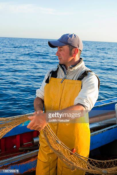 fisherman pulling in nets on boat - industrial ship stock pictures, royalty-free photos & images