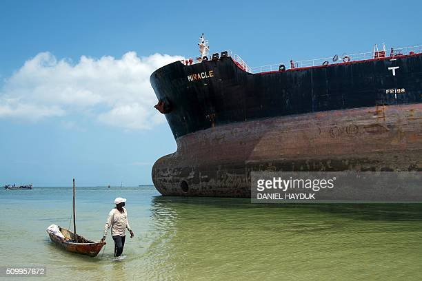 A fisherman pulls a canoe as he walks by the Marshall Islands flagged tanker vessel Miracle after it ran aground at the mouth of the Dar es Salaam's...