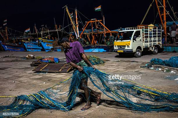 A fisherman pulls a fishing net on the quayside in Puducherry India on Saturday July 19 2014 Indias gross domestic product growth forecast for the...