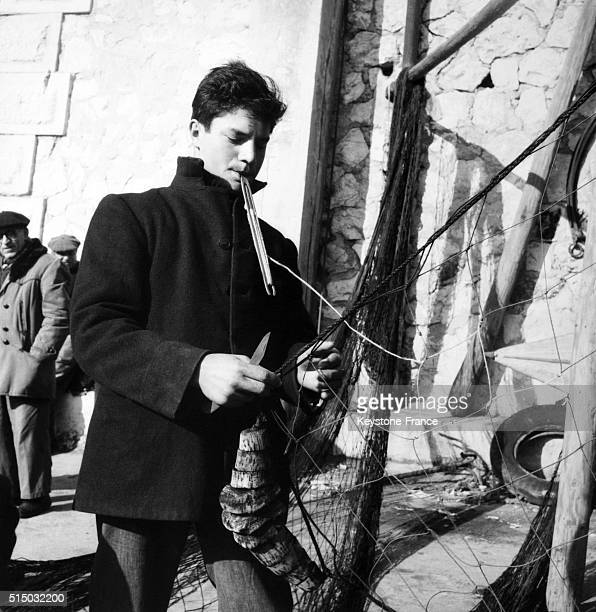 Fisherman repairing a fishing net in Marseille France in 1956