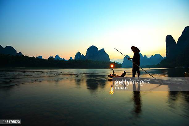 Fisherman rowing in the river in the twilight