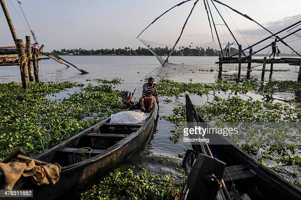 A fisherman rows his boat ashore as others work on a shoreoperated lift net at the Fort Kochi Chinese fishing nets in Cochin Kerala India on Friday...
