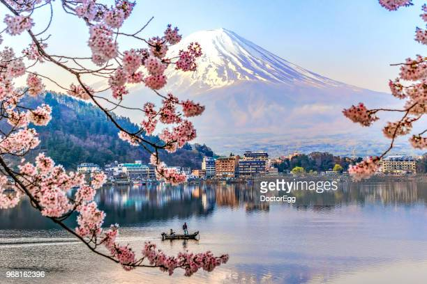 fisherman sailing boat in kawaguchiko lake and sakura with fuji mountain reflection background - japón fotografías e imágenes de stock