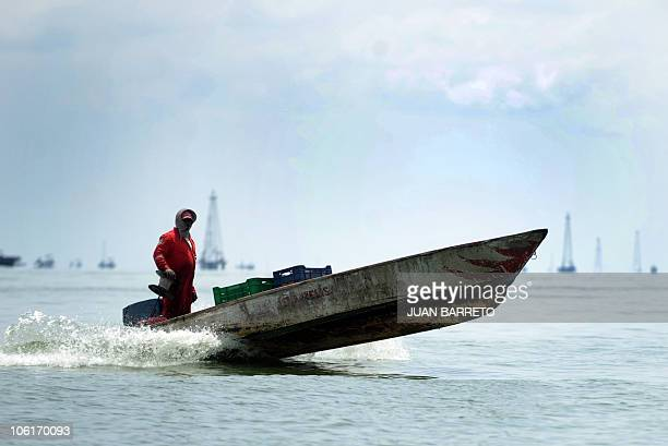 A fisherman sails his boat in front of an oil tower Maracaibo Lake located in the border state of Zulia in western Caracas on October 27 2010 AFP...