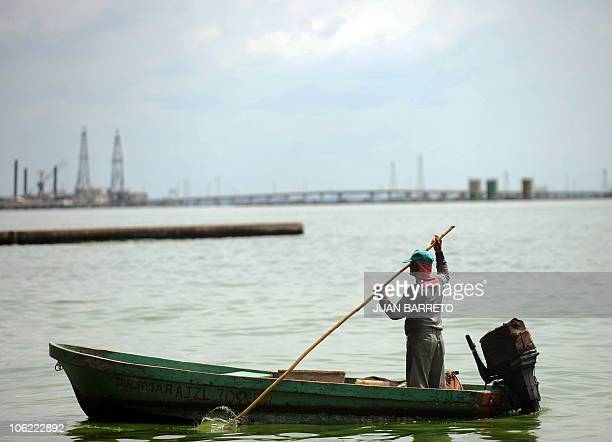 A fisherman sails his boat in front of oil towers in Maracaibo Lake located in the border state of Zulia in western Caracas on October 27 2010 AFP...