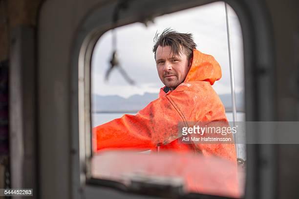 Fisherman seen through fishing boat window