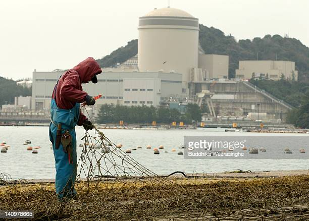 A fisherman sets up a fishing net beside Mihama No 3 reactor at the The Mihama Nuclear Power Plant which is run by Kansai Electric Power Co on March...