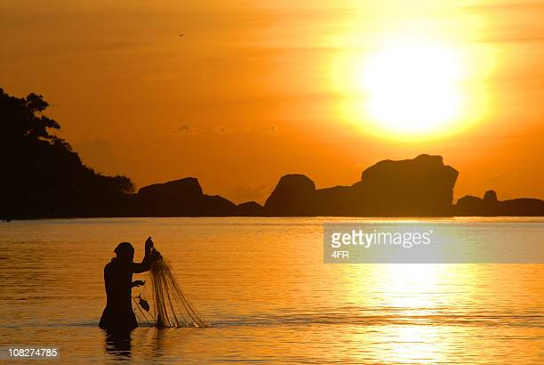 Fisherman Silhouette at Sunrise pulling in his Fishing Net