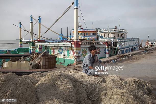 A fisherman sits on a pile of nets at a harbor in Gwadar Balochistan Pakistan on Tuesday Aug 2 2016 Gwadar is the cornerstone of Chinese President Xi...