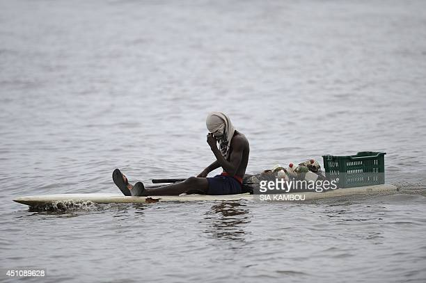 A fisherman sits on a wooden board at the Ebrie Lagoon on June 23 before the arrival of the newly purchased RPB 33 patrol boat L'Emergence...