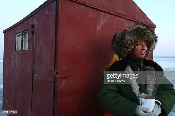A fisherman sits with a drink before setting out to catch fish from the frozen Chagan Lake during the 5th annual Chagan Lake Ice and Snow Fishing...