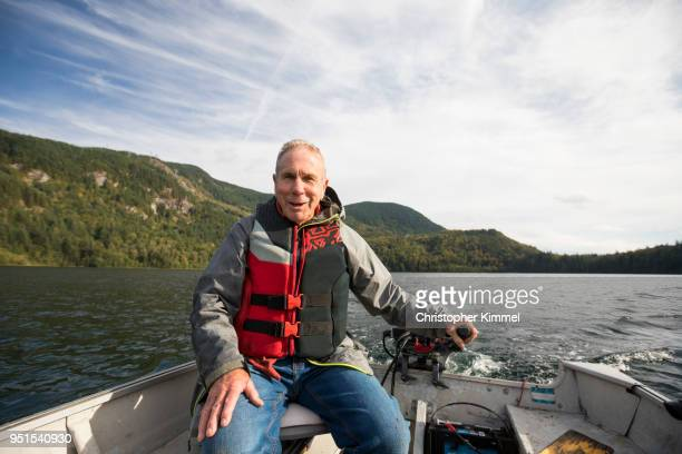 fisherman sitting in motorboat, hicks lake, harrison hot springs, british columbia, canada - small boat stock pictures, royalty-free photos & images