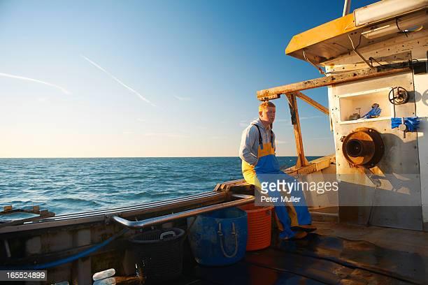 Fisherman sitting on ledge of boat