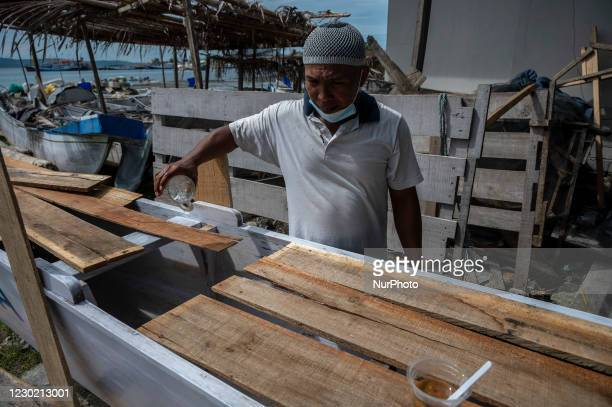 Fisherman splashes his boat with water during the new boat salvation ritual in Pantoloan Boya Village, Palu City, Central Sulawesi Province,...