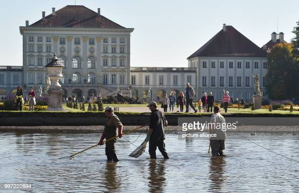 Fisherman standing during the traditional fishing out in the Nymphenburger canal with a castle to be seen in the background in Munich Germany 14...