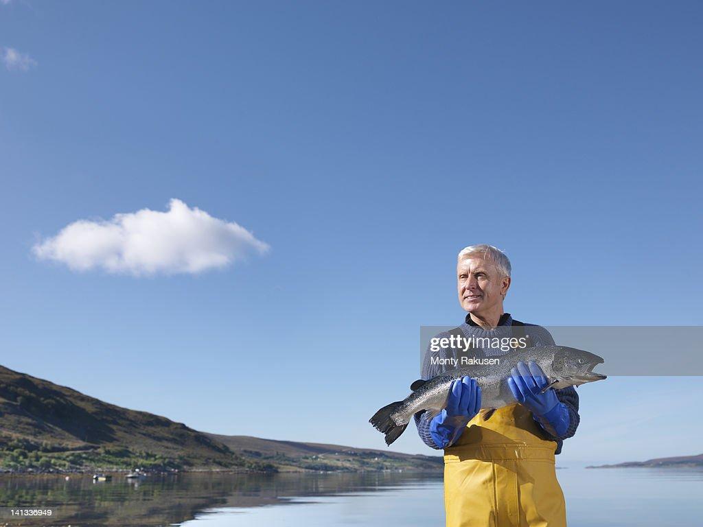 Fisherman standing in loch holding freshly caught salmon : ストックフォト