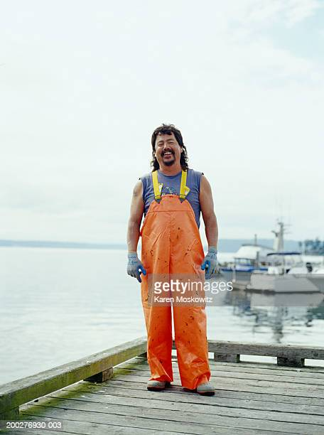 fisherman standing on dock, smiling, portrait - fisherman stock pictures, royalty-free photos & images
