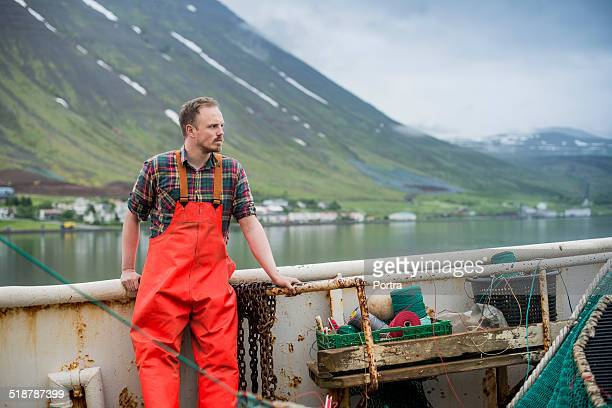 Fisherman standing on fishing boat