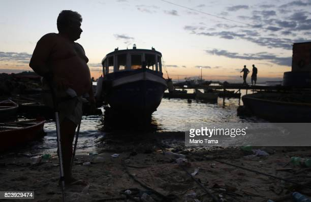 A fisherman stands along the coast of the polluted Guanabara Bay on July 25 2017 in Niteroi Brazil Nearly one year after Rio hosted the first Olympic...