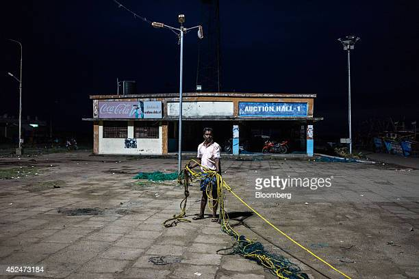 A fisherman stands holding a fishing net on the quayside in Puducherry India on Saturday July 19 2014 Indias gross domestic product growth forecast...