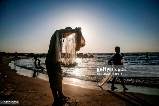 Fisherman stands holding his nets by a beach off Gaza City near sunset on August 16, 2019.