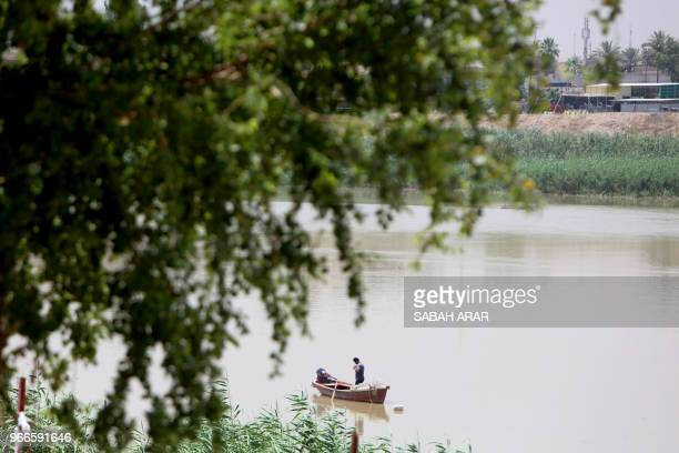 A fisherman stands next to his boat in the Tigris river in Baghdad on June 3 2018