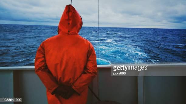 漁師の釣りボートのデッキ上で海を見つめて - 船員 ストックフォトと画像