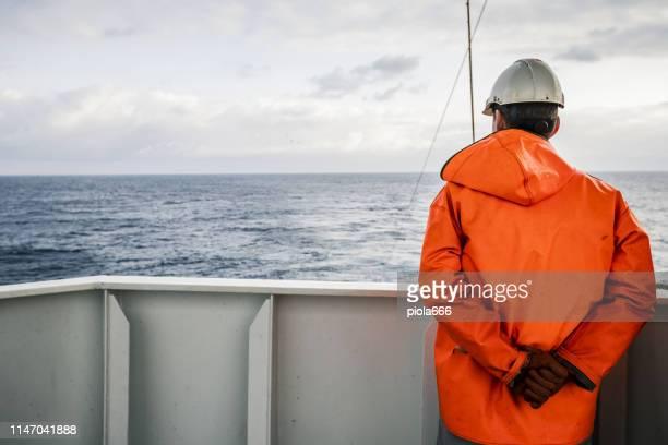 visser staren op zee op de vissersboot dek - matroos stockfoto's en -beelden
