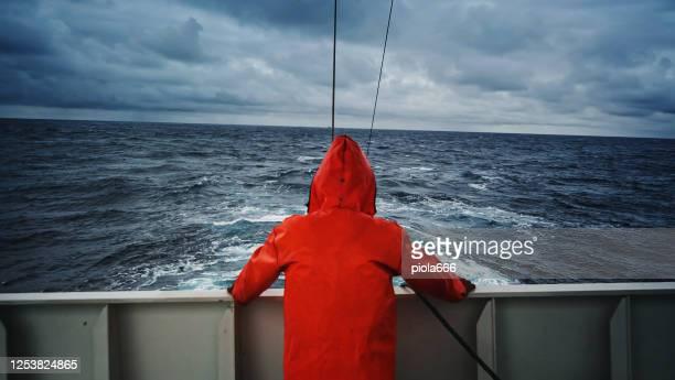 visser die bij overzees op het dek van de vissersboot, met een oranje regenjas staart - schip watervaartuig stockfoto's en -beelden