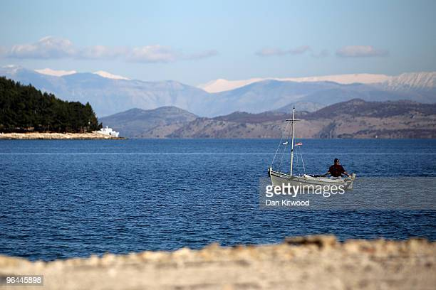 A fisherman steers his boat along the shoreline on February 5 2010 in Corfu Greece Snow covered mountains in Albania can be seen in the distance