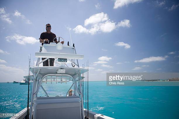 A fisherman steers his boat from the fly bridge negotiating blue-green tropical waters.