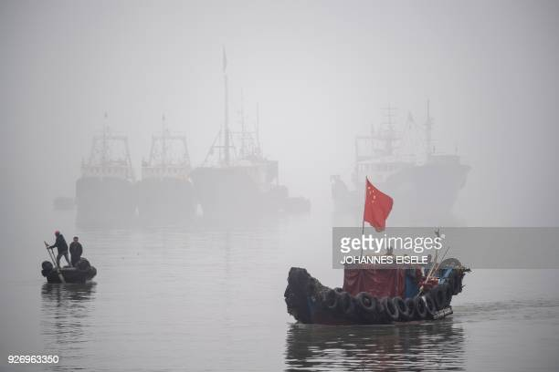 A fisherman steers his boat in the port of Huangqi village near Lianjiang in Fujian province on March 4 2018 / AFP PHOTO / Johannes EISELE