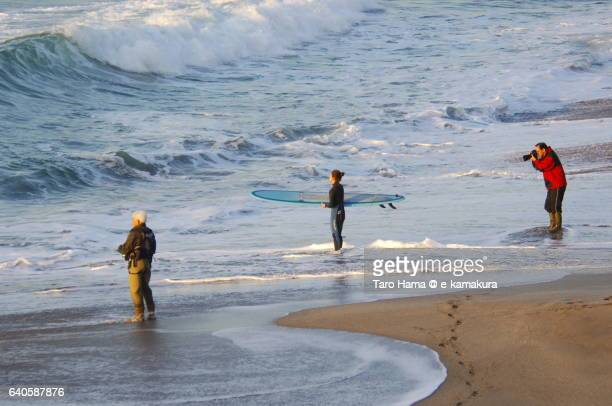 A fisherman, surfer and photographer on the morning beach
