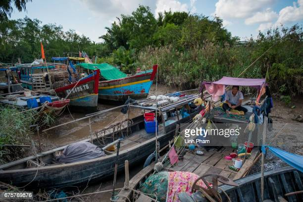 A fisherman takes a break at his boat on a sanlinizated canal in Thua Duc Village Binh Dai District Ben Tre Province Vietnam The Mekong River Delta...
