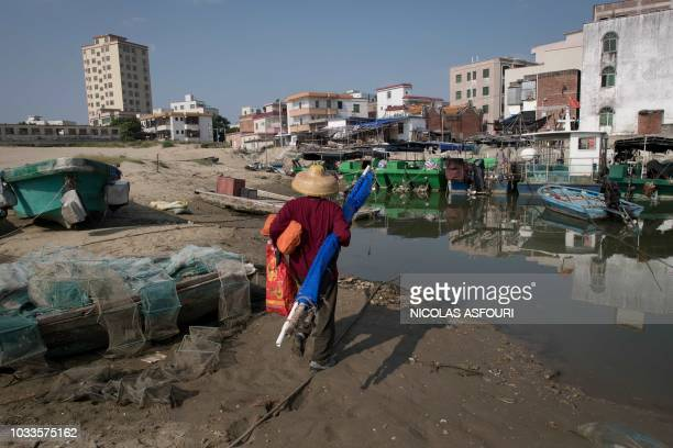 A fisherman takes away the dismantled roof of his boat ahead of the arrival of the Super Typhoon Mangkhut in Sanhe village on the outskirts of...