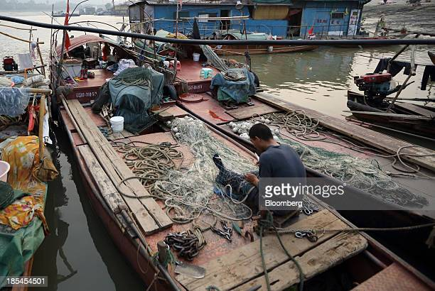 A fisherman takes care of his fishing net on a boat on the Chang Jiang river in Wuhan China on Sunday Oct 20 2013 China's economic expansion...