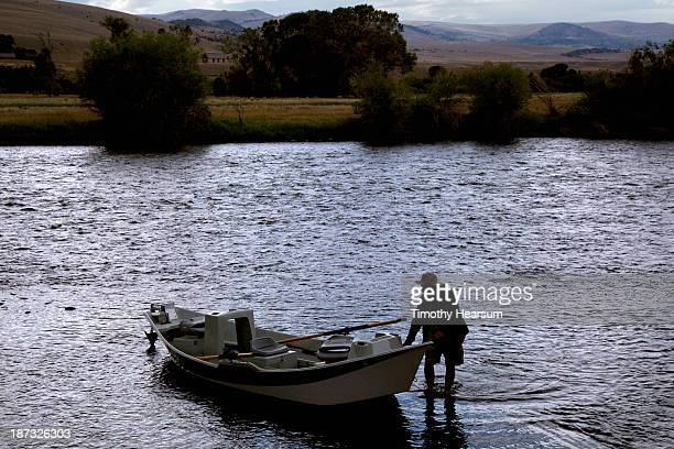 fisherman taking boat out of the water at sunset - timothy hearsum stock photos and pictures
