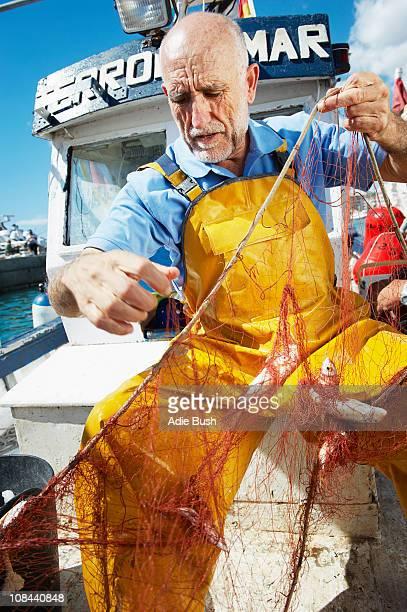 Pescador tomar pescado fuera de los NET