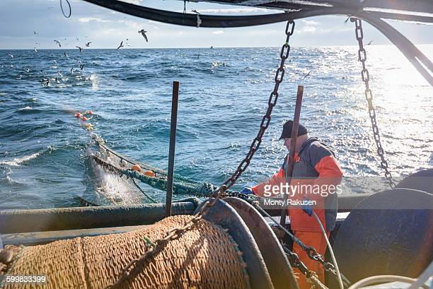 Fisherman tending nets on trawler