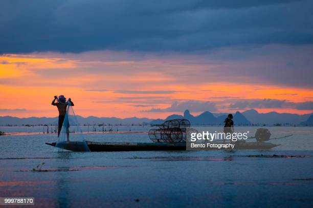 fisherman throw his net to catch to fish on the boat in twilight time - provincia di songkhla foto e immagini stock