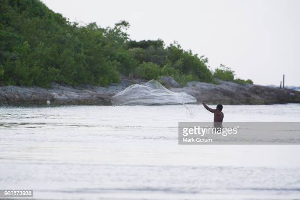 fisherman throwing net in sea against sky - french overseas territory stock pictures, royalty-free photos & images