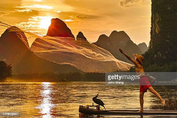 Fisherman throwing net on Li River at sunset