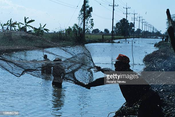 Fisherman throws his net in a canal in eastern Thailand.