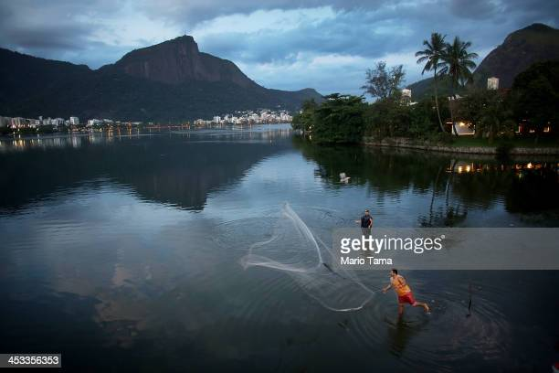 A fisherman tosses his net into Lagoa Rodrigo de Freitas which will host rowing and canoeing events in the Rio 2016 Olympic Games on December 3 2013...