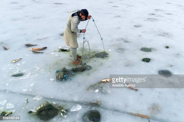 Fisherman tries to fish over the frozen 'Lake Van' as it has been frozen due to extreme cold weather during winter season in Van Turkey on December...
